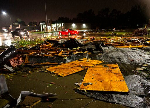 (Abigail Dollins/The Argus Leader via AP). In this Tuesday, Sept. 10, 2019 photo, vehicles drive past debris littering a street after severe weather swept through the area in Sioux Falls, S.D.