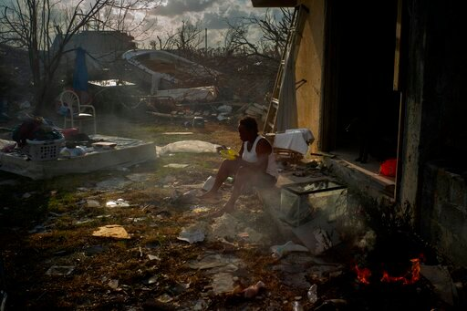 (AP Photo/Ramon Espinosa). Tereha Davis, 45, eats a meal of rice as she sits among the remains of her shattered home, in the aftermath of Hurricane Dorian in McLean's Town, Grand Bahama, Bahamas, Wednesday Sept. 11, 2019. She and others said they had n...