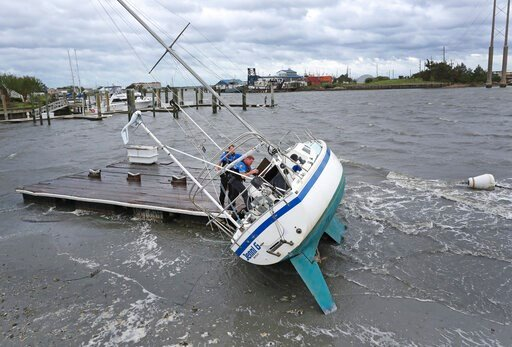 (AP Photo/Tom Copeland). Beaufort Police Officer Curtis Resor, left, and Sgt. Micheal Stepehens check a sailboat for occupants in Beaufort, N.C. after Hurricane Dorian passed the North Carolina coast on Friday, Sept. 6, 2019. Dorian howled over North C...