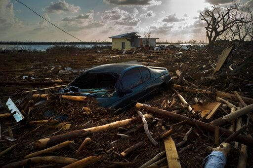 (AP Photo/Ramon Espinosa). A car is sunk in the wreckage and debris caused by Hurricane Dorian, in Mclean's Town, Grand Bahama, Bahamas, Wednesday Sept. 11, 2019. Bahamians are tackling a massive clean-up a week after Hurricane Dorian devastated the ar...