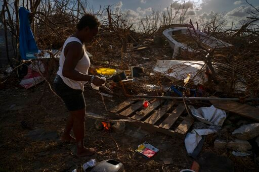 (AP Photo/Ramon Espinosa). Tereha Davis, 45, holds a plate of rice as she walks among the remains of her shattered belongings, in the aftermath of Hurricane Dorian, in McLean's Town, Grand Bahama, Bahamas, Wednesday Sept. 11, 2019. She and others said ...