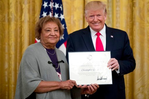 (AP Photo/Andrew Harnik, File). FILE - In this Sept. 9, 2019, file photo, President Donald Trump presents a Certificate of Commendation to Minnie Grant, the mother of Christopher Grant, one of five civilians celebrated for their heroism during a mass s...