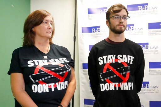 (AP Photo/Charles Rex Arbogast). Adam Hergenreder, right, and his mother Polly, attend a news conference where their attorney announced the filing of a civil lawsuit against e-cigarette maker Juul on Hergenreder's behalf Friday, Sept. 13, 2019, in Chic...