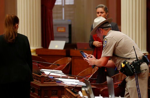 (AP Photo/Rich Pedroncelli). A California Highway Patrol Officer photographs a desk on the Senate floor after a red liquid was thrown from the Senate Gallery during the Senate session at the Capitol in Sacramento, Calif., Friday, Sept. 13, 2019. The Se...