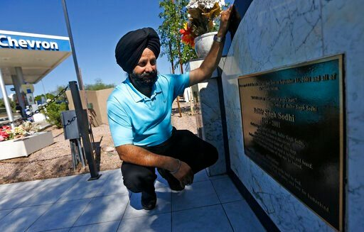 (AP Photo/Ross D. Franklin, File). FILE - In this Aug. 19, 2016, file photo, Indian Sikh immigrant Rana Singh Sodhi kneels next to a memorial in Mesa, Ariz., for his murdered brother, Balbir Singh Sodhi, who was gunned down at the site four days after ...