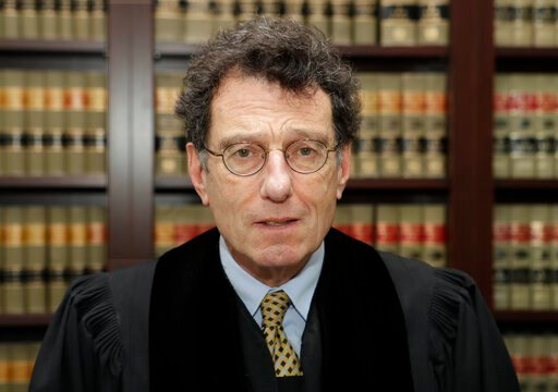 (AP Photo/Tony Dejak, File). FILE - This Jan. 11, 2018 file photo shows Judge Dan Polster in his office, in Cleveland.  Attorneys representing eight drug distributors, pharmacies and retailers facing trial for their roles in the national opioid crisis ...