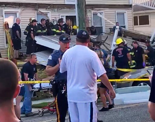 (James Macheda via AP). In this photo provided by James Macheda, one of the first responders talks to an onlooker as others carry an injured person, while some others work the scene of a building structure damage, in the background, in Wildwood, N.J., ...