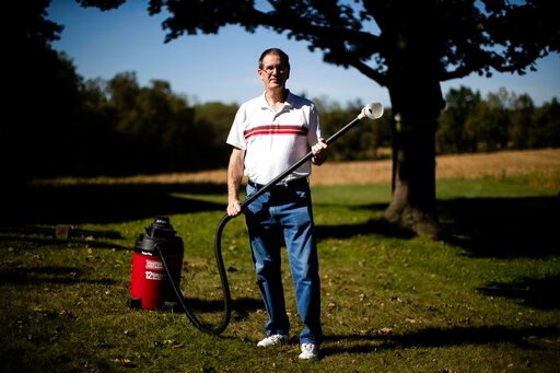 (AP Photo/Matt Rourke). In this Thursday, Sept. 19, 2019, photo, Jim Wood poses for a photograph with his wet/dry vac he uses to deal with the swarms of lanternflies that have been attacking his trees in Allentown, Pa. The spotted lanternfly has emerge...