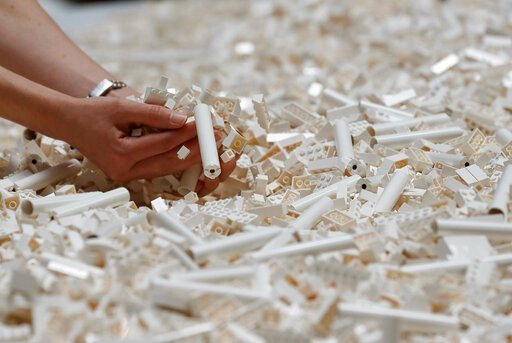 (AP Photo/Frank Augstein, File). FILE - In this Friday July 26, 2019, file photo, a visitor looks through Lego pieces provided for a project at the Tate Modern, in London. Lego is testing a way for customers to ship their unwanted bricks back and get t...