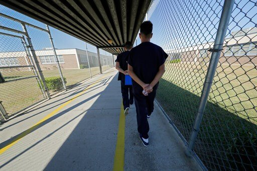 (AP Photo/Gerald Herbert). Detainees walk with their hands clasped behind their backs along a line painted on a walkway inside the Winn Correctional Center in Winnfield, La., Thursday, Sept. 26, 2019. Detainees are required to walk from site to site wi...