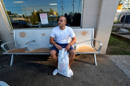 (AP Photo/Gerald Herbert). Pedro Cordoves Diaz, a 26-year-old from Cuba who was just released from the Winn Correctional Center, waits with his sole bag of belongings, at a bus station over 55 miles away, to travel to relatives in New Jersey, in Alexan...
