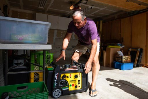 (Randy Vazquez/San Jose Mercury News via AP). Joe Wilson pulls his generator out in the garage of his home, which is in an area that is expected to lose power early Wednesday, in the East Foothills area of San Jose, Calif., Tuesday, Oct. 8, 2019. Milli...