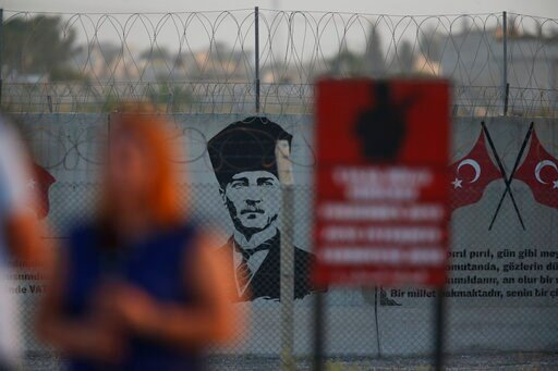 (AP Photo/Lefteris Pitarakis). A graffiti of modern Turkey's founder Mustafa Kemal Ataturk is seen on the Turkish side of the border between Turkey and Syria, as a TV journalist works in Akcakale, Sanliurfa province, southeastern Turkey, Tuesday, Oct. ...