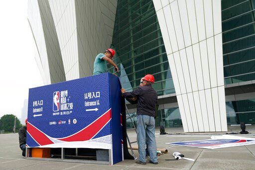 (AP Photo). Workers dismantle signage for an NBA fan event scheduled to be held on Wednesday night at the Shanghai Oriental Sports Center in Shanghai, China, Tuesday, Oct. 8, 2019. Chinese state broadcaster CCTV announced Tuesday it will no longer air ...