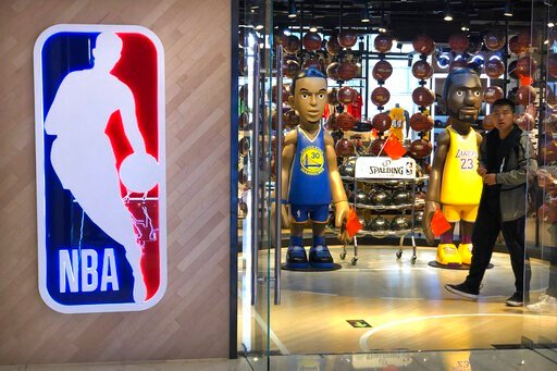 (AP Photo/Mark Schiefelbein). A man walks past statues of NBA players Stephen Curry of the Golden State Warriors, left, and Lebron James of the Los Angeles Lakers holding Chinese flags in the entrance of an NBA merchandise store in Beijing, Tuesday, Oc...