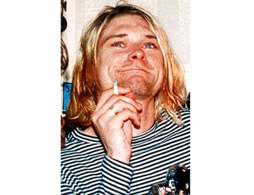 (AP Photo/Mark J. Terrill, File). FILE - This 1993 file photo shows Kurt Cobain, the lead singer of the U.S. rock band Nirvana. A custom made Fender guitar and olive green cardigan sweater owned by Cobain are among the rock and roll items up for auctio...