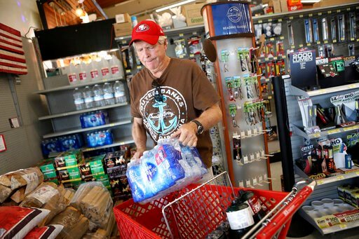 (Anda Chu/San Jose Mercury News via AP). James Cooke is shown buying water bottles along with propane tanks and batteries at a ACE Hardware store as he prepares for a possible power shutdown in Los Gatos, Calif., on Tuesday, Oct. 8, 2019. Millions of p...