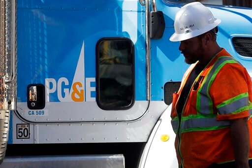 (AP Photo/Jeff Chiu, File). FILE - In this Aug. 15, 2019, file photo, a Pacific Gas & Electric worker walks in front of a truck in San Francisco. Two years to the day after some of the deadliest wildfires tore through Northern California wine count...