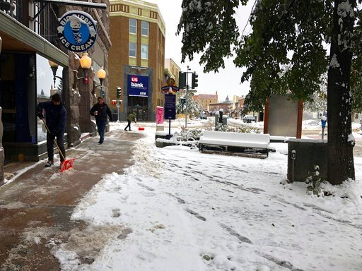(AP Photo/Matt Volz). People clear the sidewalk after a fall snowstorm in Helena, Mont., on Wednesday, Oct. 9, 2019. The central Rocky Mountain region recieved its first dose of wintry weather. Mountainous areas recently hit by snowfall measured in fee...