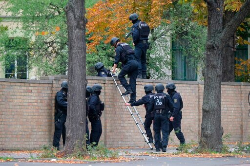 (Sebastian Willnow/dpa via AP). Police officers cross a wall at a crime scene in Halle, Germany, Wednesday, Oct. 9, 2019 after a shooting incident. A gunman fired several shots on Wednesday in the German city of Halle. Police say a person has been arre...