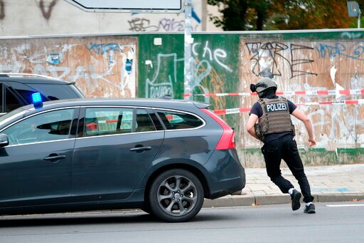 (Sebastian Willnow/dpa via AP). Police officer runs on a road in Halle, Germany, Wednesday, Oct. 9, 2019. One or more gunmen fired several shots on Wednesday in the German city of Halle. Police say a person has been arrested after a shooting that left ...