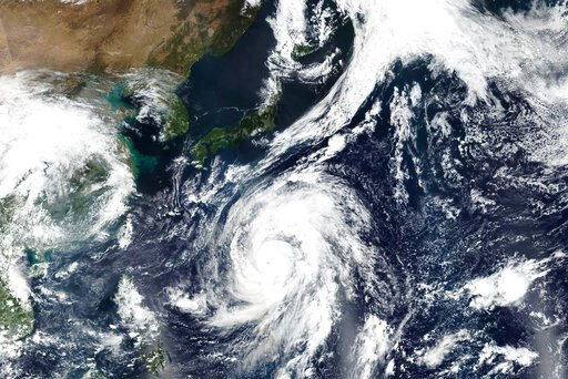 (EOSDIS) via AP). This Oct. 9, 2019, satellite photo taken by NASA-NOAA's Suomi NPP satellite shows typhoon Hagibis approaching Japan, top.  Japan's weather agency is warning a powerful typhoon may bring torrential rains to central Japan over the weeke...