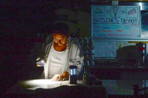 (Alan Dep/Marin Independent Journal via AP). Carlos Lama of Bayside Cafe, which was among businesses to lose power due to PG&E's public safety power shutoff, uses an LED lamp and light from his phone at the counter of the restaurant in Sausalito, C...