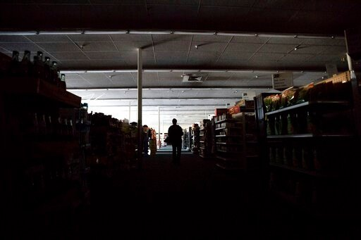 (AP Photo/Noah Berger). Shift supervisor James Quinn walks through a darkened CVS Pharmacy as downtown Sonoma, Calif., remains without power on Wednesday, Oct. 9, 2019. Pacific Gas and Electric has cut power to more than half a million customers in Nor...