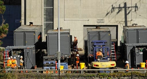 (AP Photo/Ben Margot). Crews work to connect generators in effort to keep the Caldecott Tunnel open to traffic during a possible power outage in the afternoon on Wednesday, Oct. 9, 2019, in Oakland, Calif. Pacific Gas & Electric has cut power to mo...