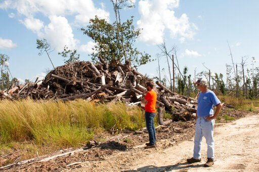 (AP Photo/Bobby Caina Calvan). In this Oct. 5, 2019 photo, Daniel Leonard and his father Joe, right, stand near a heap of lumber on their family's property.  The massive storm killed more than two dozen people in northern Florida, destroyed hundreds of...