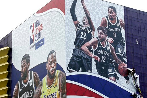 (AP Photo/File). In this Oct. 9, 2019, photo, a worker takes down a billboard advertising an NBA preseason basketball game on Thursday between the Los Angeles Lakers and Brooklyn Nets in Shanghai, China. The NBA has postponed Wednesday's scheduled medi...