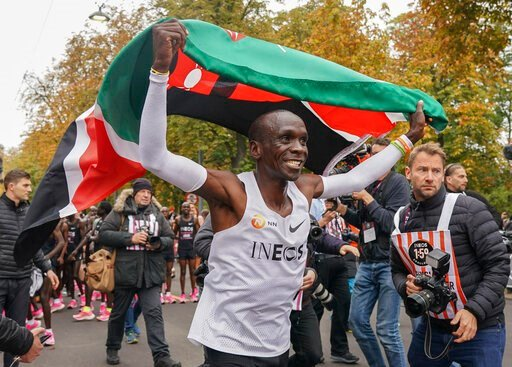 (Jed Leicester/The INEOS 1:59 Challenge via AP). Eliud Kipchoge celebrates with the Kenyan flag after breaking the historic two hour barrier for a marathon in Vienna, Saturday, Oct. 12, 2019. Eliud Kipchoge has become the first athlete to run a maratho...
