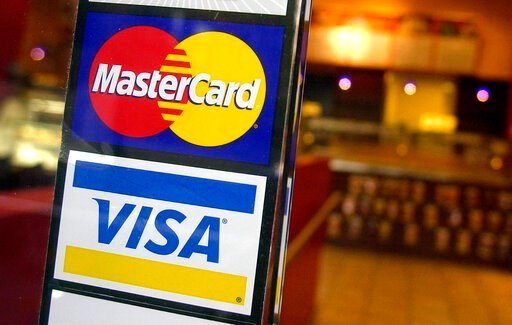 (AP Photo/Mark Lennihan, File). FILE - This April 22, 2005, file photo, shows logos for MasterCard and Visa credit cards at the entrance of a New York coffee shop. Visa and Mastercard are dropping out of Facebook's Libra project, a potentially fatal bl...