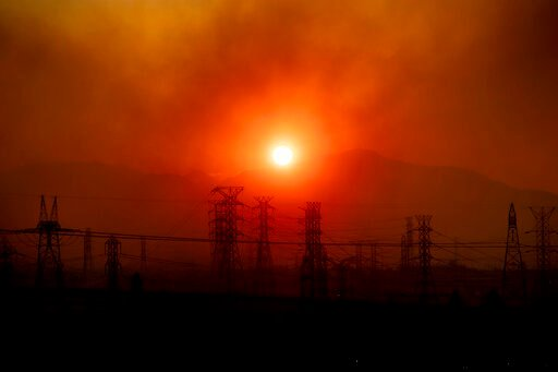 (AP Photo/Noah Berger). Smoke from the Saddleridge Fire hangs above power lines as the sun rises in Newhall, Calif., on Friday, Oct. 11, 2019. An aggressive wildfire in Southern California seared its way through dry vegetation Friday and spread quickly...