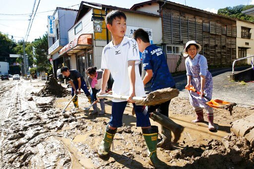 (Kyodo News via AP). Students and residents scoop dirt as the town is flooded Typhoon Hagibis, in Marumori, Miyagi prefecture, northern Japan, Sunday, Oct. 13, 2019. Rescue efforts for people stranded in flooded areas are in full force after a powerful...