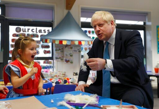 (AP Photo/Alastair Grant, Pool). Britain's Prime Minister Boris Johnson gestures as he participates in an art class with Scarlet Fickling aged 4, in at St Mary's and All Saints Primary School in Beaconsfield, England, Friday, Oct. 11, 2019.