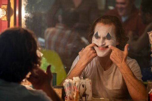 "(Niko Tavernise/Warner Bros. Pictures via AP). This image released by Warner Bros. Pictures shows Joaquin Phoenix in a scene from the film ""Joker."""