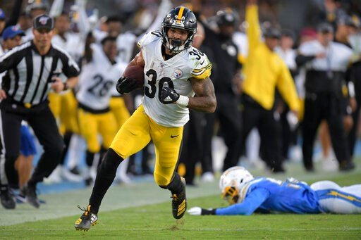 (AP Photo/Kyusung Gong). Pittsburgh Steelers running back James Conner, left, gets by Los Angeles Chargers outside linebacker Jatavis Brown as he runs for a touchdown during the first half of an NFL football game, Sunday, Oct. 13, 2019, in Carson, Calif.