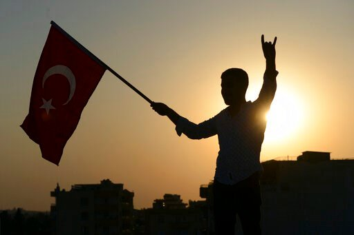 (Ismail Coskun/IHA via AP). A Turkish youth celebrates with a national flag after news about Syrian town of Tal Abyad, in Turkish border town of Akcakale, in Sanliurfa province, Sunday, Oct. 13, 2019. Turkey's official Anadolu news agency, meanwhile, s...