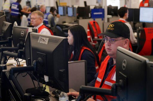 (AP Photo/Jeff Chiu, File). FILE - In this Oct. 10, 2019, file photo, Pacific Gas & Electric employees work in the PG&E Emergency Operations Center in San Francisco. Experts say it's hard to know what might have happened had the power stayed on...