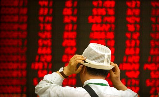 (AP Photo/Mark Schiefelbein, File). FILE - In this Sept. 5, 2019, file photo, an investor adjusts his hat as he monitors stock prices at a brokerage house in Beijing. Asian stock markets have risen after Washington and Beijing announced a truce on tari...