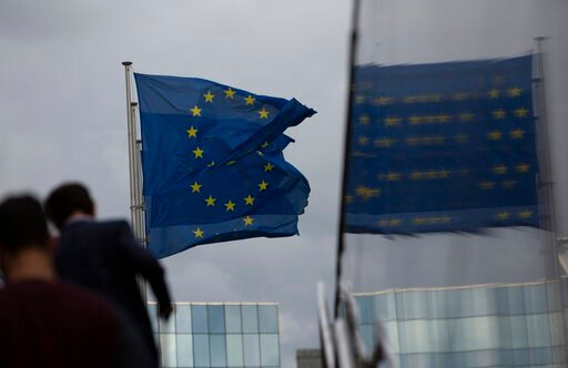 (AP Photo/Virginia Mayo). European Union flags flap in the wind as two people walk up a set of stairs outside EU headquarters in Brussels, Sunday, Oct. 13, 2019. Technical talks on Brexit continued in Brussels over the weekend with European Union Brexi...