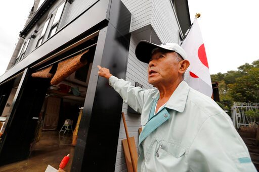 (AP Photo/Eugene Hoshiko). Kazuo Sato shows the flood water level of his house as he cleans up Monday, Oct. 14, 2019, in Kawagoe City, Japan. Typhoon Hagibis dropped record amounts of rain for a period in some spots, according to meteorological officia...