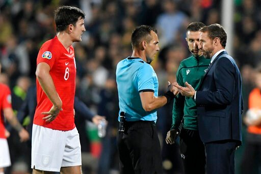 (AP Photo/Andreea Alexandru). England manager Gareth Southgate, right, speaks with Referee Ivan Bebek during the Euro 2020 group A qualifying soccer match between Bulgaria and England, at the Vasil Levski national stadium, in Sofia, Bulgaria, Monday, O...