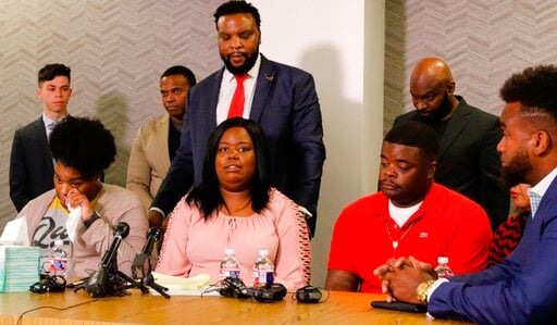 (Irwin Thompson/The Dallas Morning News via AP). Amber Carr, left, wipes a tear as her sister Ashley Carr, center, talks about their sister, Atatiana Jefferson, as their brother, Adarius Carr, right and attorney Lee Merritt, standing, listen during a n...