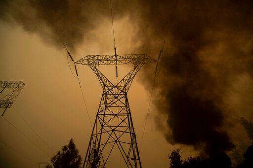 (AP Photo/Noah Berger, File). FILE - In this Nov. 9, 2018, file photo, smoke billows around power transmission lines as the Camp Fire burns in Big Bend, Calif. Experts say it's hard to know whether keeping millions of Californians in the dark prevented...