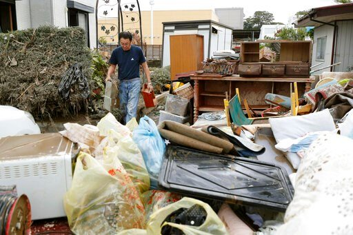 (Kyodo News via AP). A man carries household goods out of a flooded house in Motomiya, Fukushima prefecture, Japan Tuesday, Oct. 15, 2019. Typhoon Hagibis dropped record amounts of rain for a period in some spots, according to meteorological officials,...