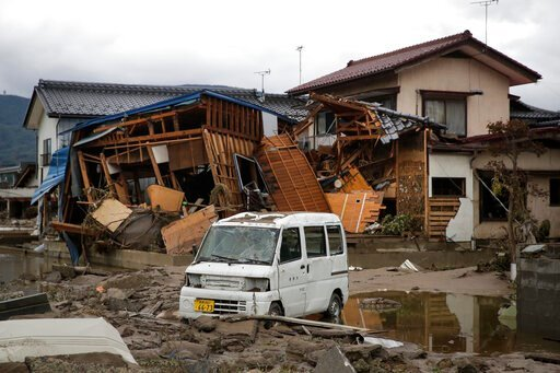 (AP Photo/Jae C. Hong). A vehicle sits in front of a home destroyed by Typhoon Hagibis Tuesday, Oct. 15, 2019, in Nagano, Japan. More victims and more damage have been found in typhoon-hit areas of central and northern Japan, where rescue crews are sea...