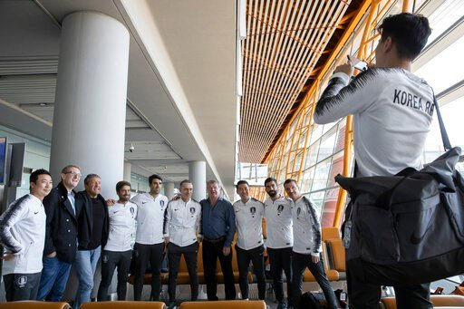 (AP Photo/Ng Han Guan). Members of the South Korean football team pose for a photo before boarding an Air China flight to Pyongyang for a World Cup qualifier match against North Korea from the airport in Beijing on Monday, Oct. 14, 2019.