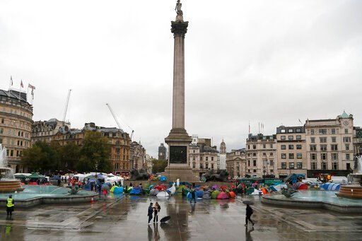 (AP Photo/Frank Augstein). Protestors of the environmental activist group extinction rebellion camp during a demonstration during a rainy morning at Trafalgar Square in London, Monday, Oct. 14, 2019.